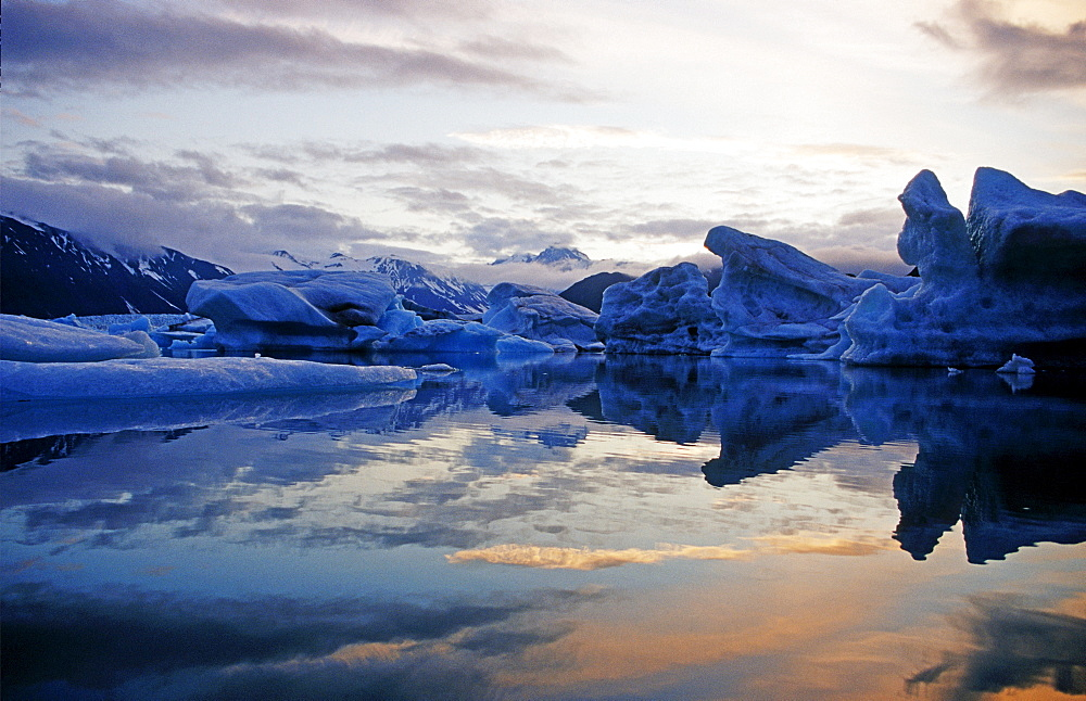 Icebergs reflected on water at sunset, Kenai Fjords National Park, Alaska, USA