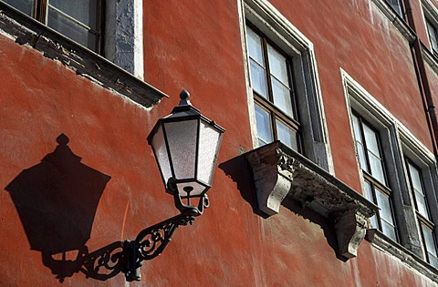A forged historical road lamp is attached to the front of an old house