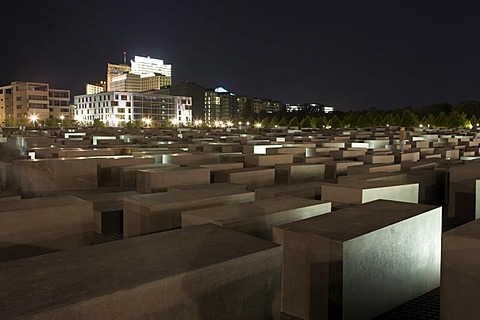 The lit Holocaust memorial at night with view of the multistoried buildings at the Potsdamer place, Berlin, Germany