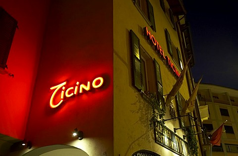 Hotel and restaurant Tessin with lit writing in the old part of town of Lugano in the evening.
