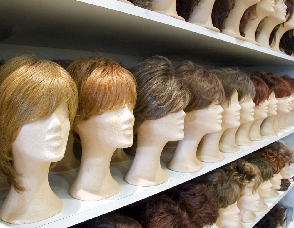 Decorative wigs for ladies placed on styrofoam heads on a rack