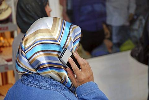 Woman with headscarf and mobile phone, Urfa, Anatolia, Turkey
