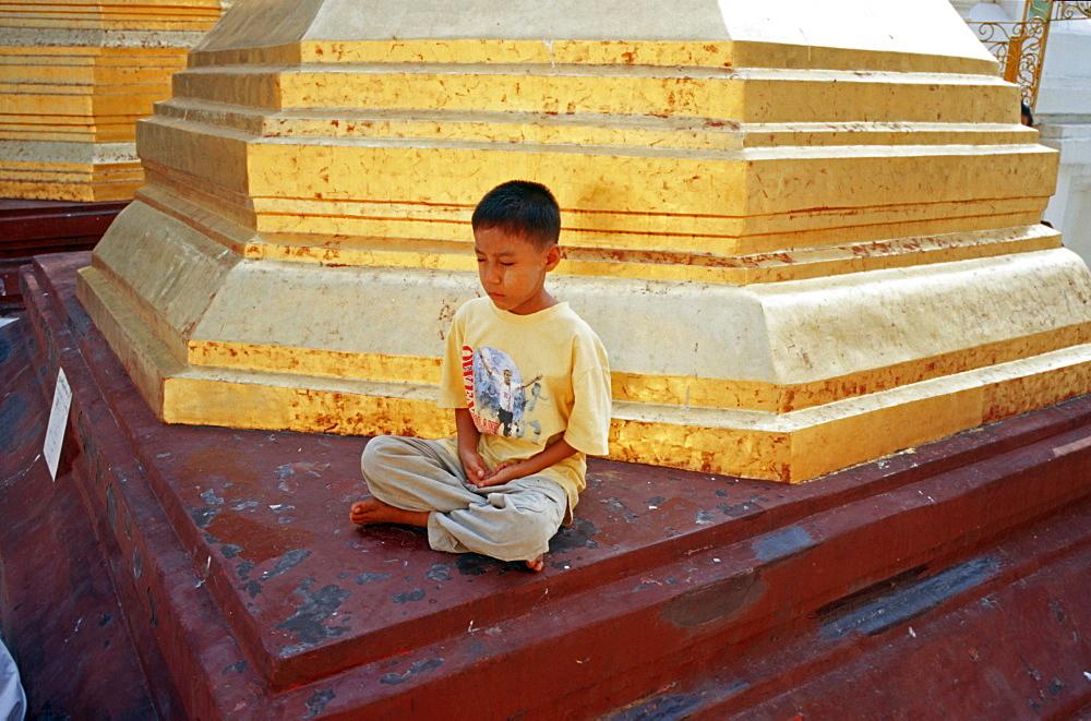 Young Burmese meditating in the Shwedagon Pagoda of Yangon, Burma, Asia