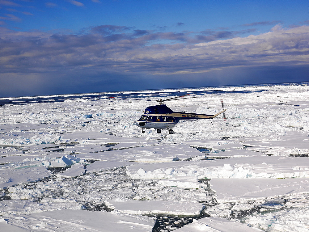 Helicopter flying above sea ice, Antarctica