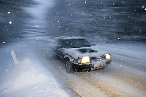 Car at snow flurry road traffic in winter Bavaria Germany