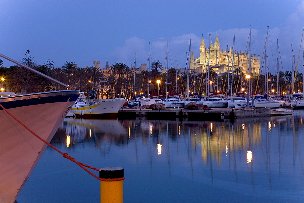 Fishing boats in the harbour at dusk and La Seu Cathedral (back), Palma, Majorca, Balearic Islands, Spain