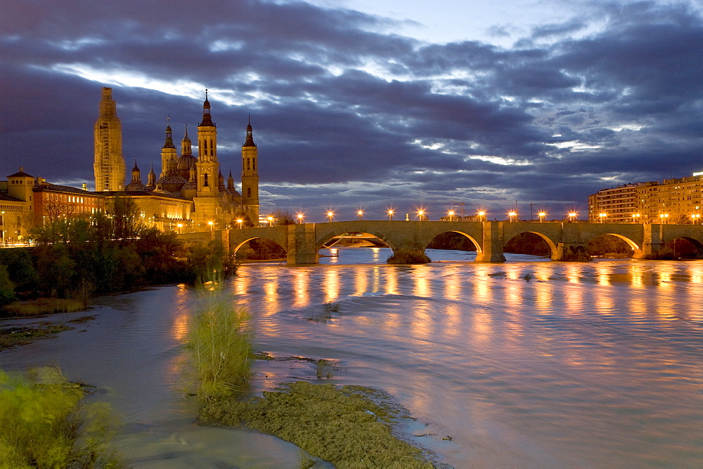 Basilica del Pilar cathedral, Puente de Piedra bridge and the Ebro River lit by street lamps under a twilight sky, dusk in Saragossa or Zaragoza, Aragon, Spain, Europe
