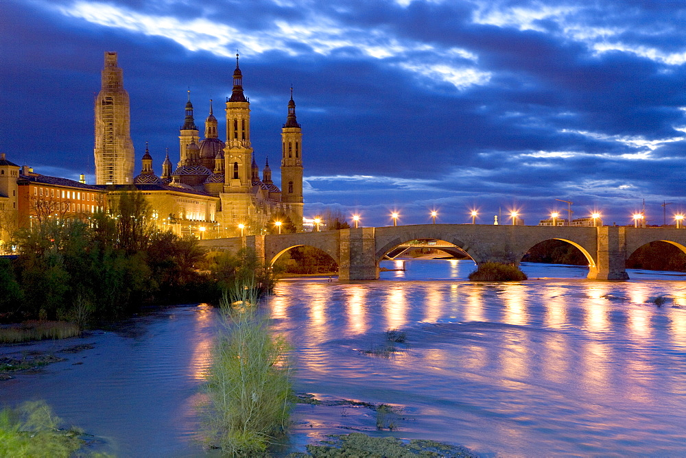 Basilica del Pilar, Basilica of Our Lady of the Pillar beside the Ebro River and the Puente de Piedra Bridge under an evening sky bathed in street lights, Zaragoza (Saragossa), Aragon, Spain