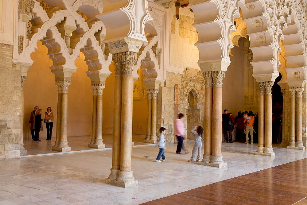 Tourists beneath the ornate stone carved arched passageway of the Santa Isabel Patio, Palacio de Aljaferia palace, Moorish architecture, Zaragoza, Saragossa, Aragon, Spain
