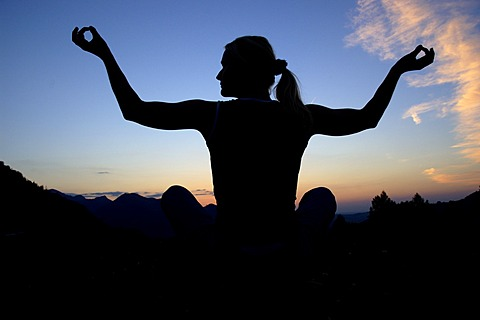 Woman doing yoga in the evening, silhouette