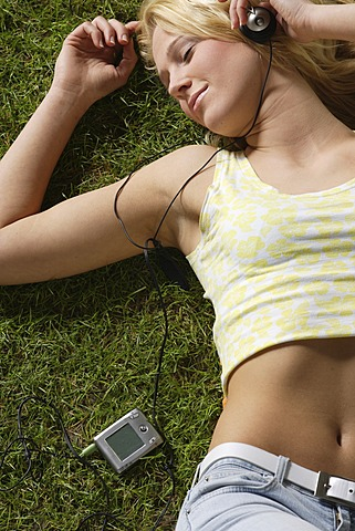Blonde girl listening to music on a MP3 player lying on a lawn
