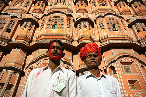 Indian men with turban and red colour in the face are standing in front of palace of the winds Jaipur Holi Festival Rajasthan India