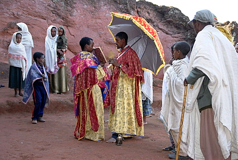 Ethiopian Orthodox Christianity priest reads out of the holy bible with believers in front of the rock hewn church Beta Marqorewos Lalibela Ethiopia
