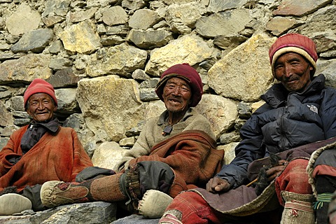 Three friendly man in traditional dress made of wool sit at a wall Phu Nar-Phu Annapurna Region Nepal