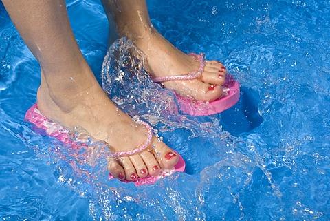 Feet wearing flip-flops in a paddling pool