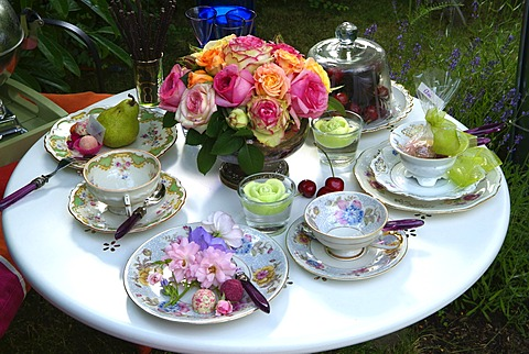 Decorated table with porcelain dishes and historic roses rosa