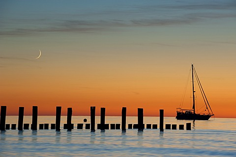 Sailboat, moon and breakwaters in the evening light, sea resort of Zingst, Fischland-Darss-Zingst, Baltic Sea, Mecklenburg, Pomerania, Germany, Europe