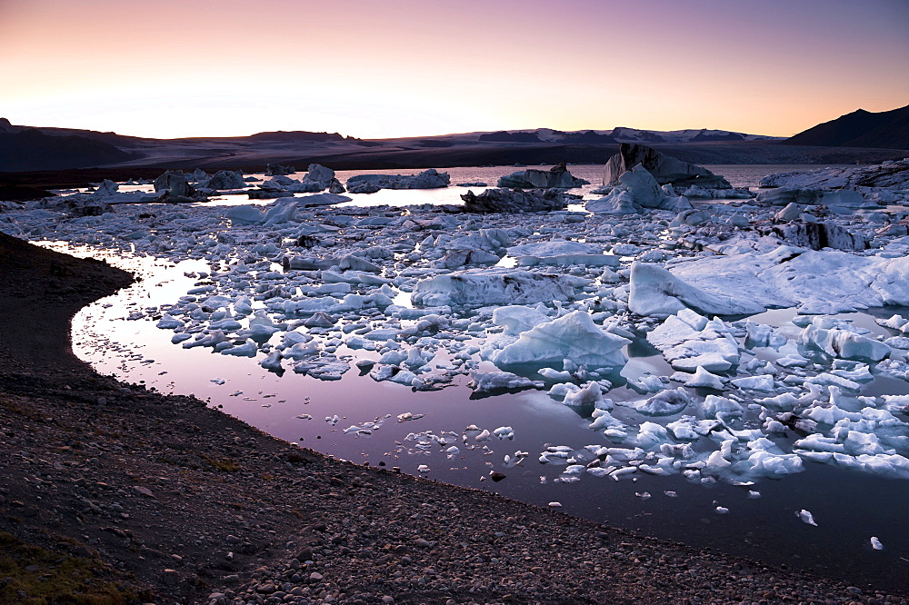 Blue and black icebergs and ice crystals in the evening light, Joekulsárlón glacial lagoon, Vatnajoekull glacier, Austurland, eastern Iceland, Iceland, Europe