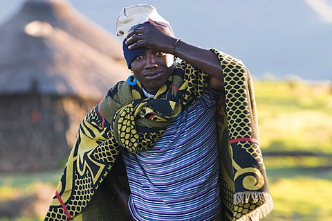 Young Basotho man wearing a traditional costume, a hut at the back, Drakensberg, Kingdom of Lesotho, southern Africa
