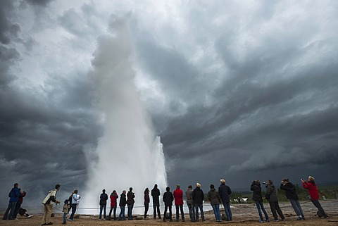Tourists watching a steam and water column, Stokkur geyser against the light, Haukadalur Valley, Golden Circle, Su√∞urland, South Iceland, Iceland, Europe