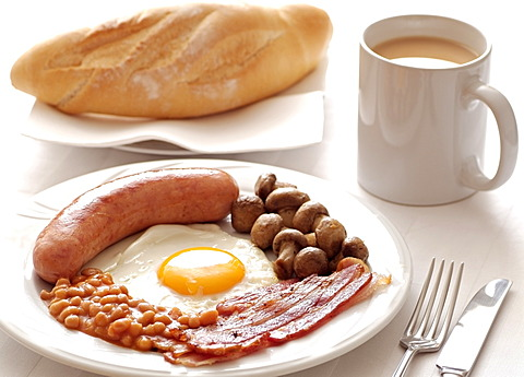 Traditional English Cooked Breakfast of Sausage, Egg, Bacon, Mushrooms and Beans. Served with a Mug of Tea.