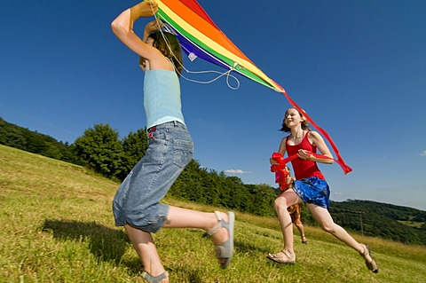 Two girls running with a kite in a meadow in the Black Forest, Baden-Wuerttemburg, Germany, Europe