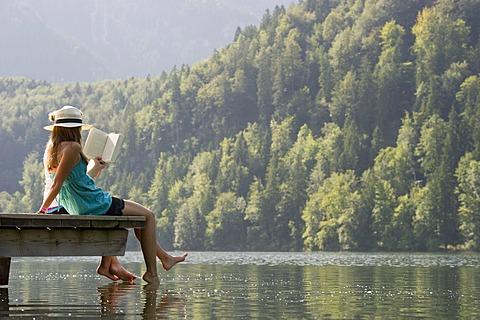 Young women sitting on a landing stage on Lake Schwansee near Fuessen, Allgaeu region, Bavaria, Germany, Europe