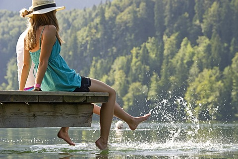 Young women sitting on a landing stage on Lake Schwansee near Fuessen, Allgaeu region, Bavaria, Germany, Europe