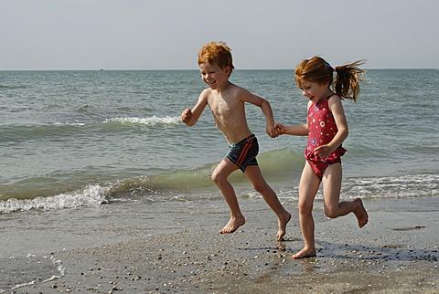 Two children running on the beach