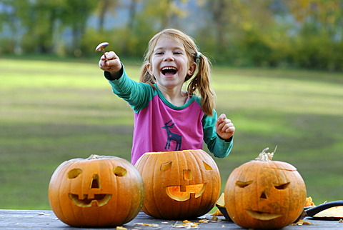Girl carving a jack-o-lantern from a pumpkin for Halloween