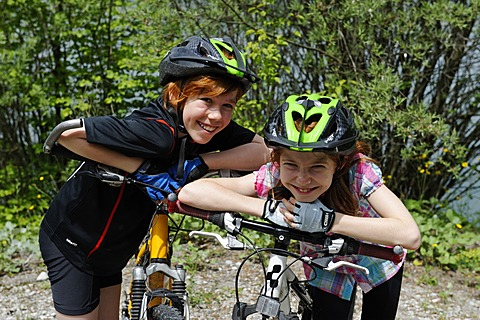 Two children, boy and girl with mountain bikes and helmets