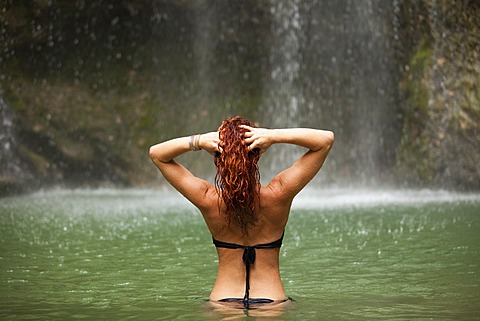 Red-haired woman standing in the water near a waterfall, from behind, Austria
