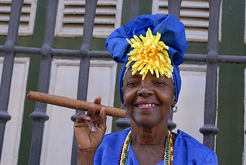 Woman wearing traditional clothes holding a cigar, Havana, Cuba