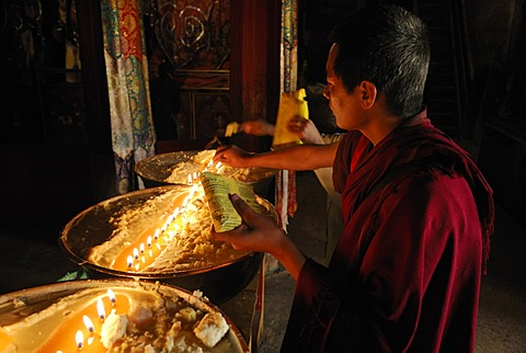 Pilgrim and Tibetan monks refilling the brass bow with yak butter, Samye Monastery, Tibet, China, Asia