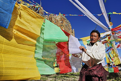 Tibetan pilgrim hanging prayer flags for the upcoming ceremony on Namtso Lake, Heavenly Lake, Tibetan, China, Asia