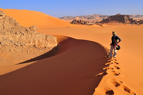 Woman climbing a sanddune at Tin Merzouga, Acacus Mountains or Tadrart Acacus range, Tassili n'Ajjer National Park, Unesco World Heritage Site, Algeria, Sahara, North Africa