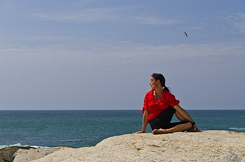 Woman in a yoga position, Ardha Matsyendrasana, by the sea in Kanyakumari, Tamil Nadu, India, Asia