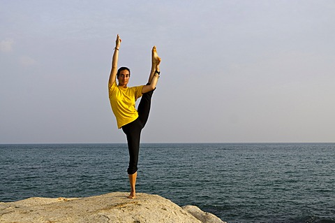 Woman in a yoga position, Anjaneyasana, by the sea in Kanyakumari, Tamil Nadu, India, Asia