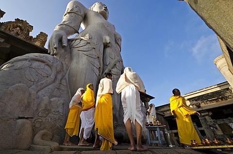 Jain pilgrims are reciting religious texts at the feet of the gigantic statue of Gomateshwara in Sravanabelagola, Karnataka, India, Asia