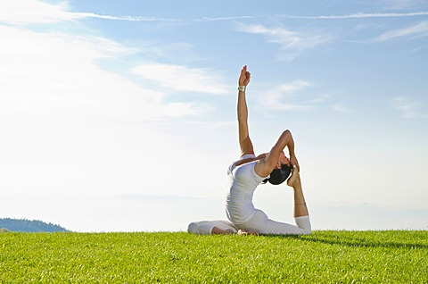 Young woman practising Hatha yoga outdoors, showing the pose kapotasana, dove pose, pigeon pose, Nove Mesto, Okres Teplice, Czech Republic, Europe
