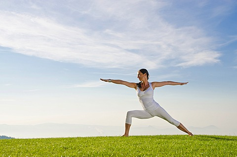 Young woman practising Hatha yoga outdoors, showing the pose virabhadrasana II, proud warrior, Nove Mesto, Okres Teplice, Czech Republic, Europe