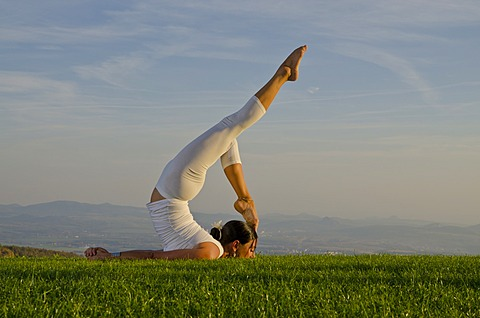 Young woman practising Hatha yoga outdoors, showing the pose shalabhasana, locust, Nove Mesto, Okres Teplice, Czech Republik, Europe