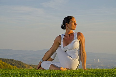 Young woman practising Hatha yoga outdoors, showing the pose ardha matsyendrasana, half spinal twist, Nove Mesto, Okres Teplice, Czech Republik, Europe