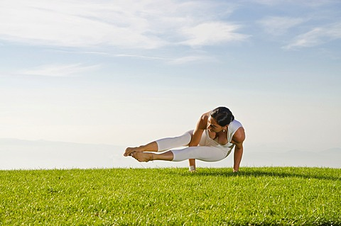 Young woman practising Hatha yoga outdoors, showing the pose kakasana, bakasana, dvi-pada-koundinyasana, variation of crow pose, Nove Mesto, Okres Teplice, Czech Republic, Europe
