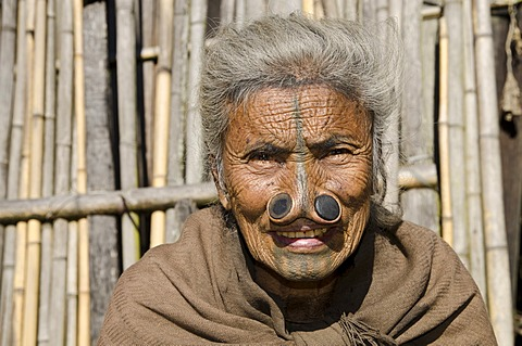 Old Apatani woman with the traditional noseplugs and tattoos, in front of her house, Hong village, Arunachal Pradesh, India, Asia