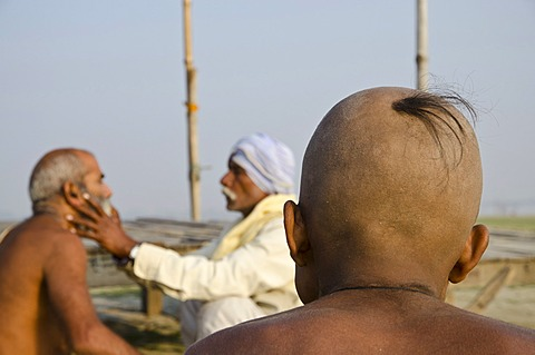 Shaving the head as part of a religious ritual, performed at Sangam, the confluence of the holy rivers Ganges, Yamuna and Saraswati, in Allahabad, Uttar Pradesh, India, Asia
