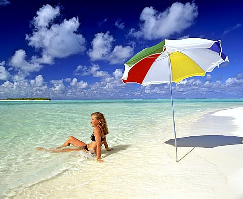 Young woman laying in shallow water, umbrella, paradise beach, Maldives, Indian Ocean