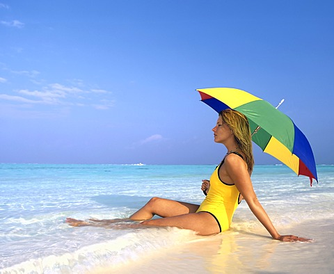Young woman sitting in shallow water with sun umbrella, Maldives, Indian Ocean