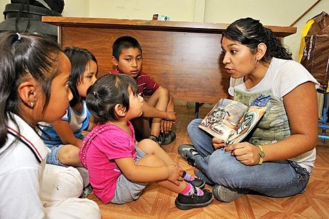 Child care worker of the Mexican non-governmental organization CIDES reading a picture book to indigenous children in a slum, Ciudad de Mexico, Mexico City, Mexico, Central America