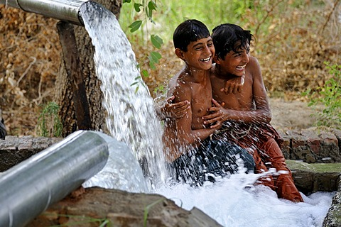 Children cooling off in the catchment of a spring fed by water pipes, Basti Lehar Walla village, Punjab, Pakistan, Asia